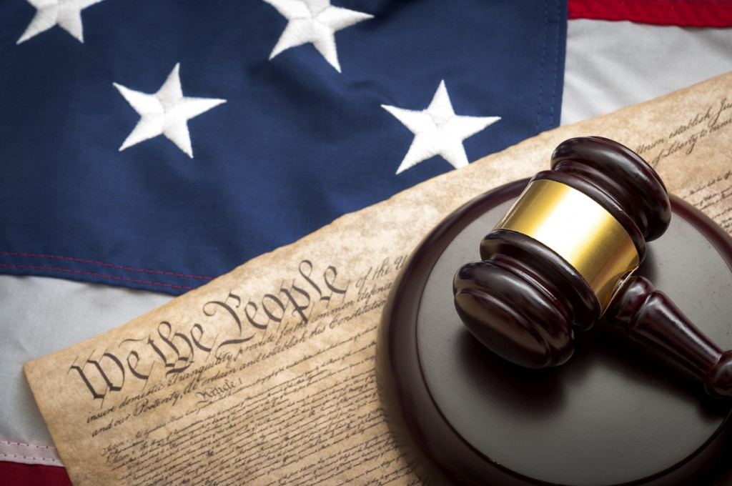 American flag, US constitution and a judge's gavel symbolizing the American justice system or the Judicial Branch of government ( Judiciary )